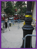 Street scene with lightpole with crime scene tape tied to it.