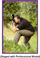 Man with camera crouching in the bushes (Staged with Professional Model).