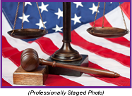 Staged photo with a gavel and scales of justice in front of an American flag.