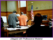 Man in orange jumpsuit with his lawyer in a courtroom (Staged with Professional Models).