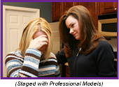 Counselor comforting a crying woman (Staged with professional models.)